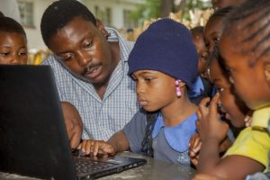 Phillip teaching young girls basic computer skills